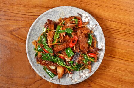 Delicious salty dried fish stir-fry with chili and scallion on plate