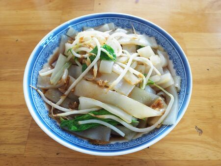 A bowl of rice noodles on wood table