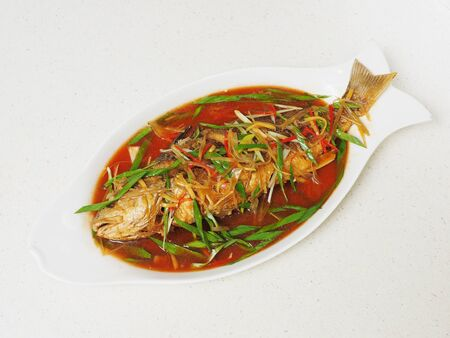 Braised yellow croaker in soy sauce on white plate Stock Photo