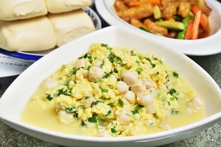 Scrambled egg with seafood and green onions in white plate