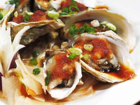 Opened oysters with sauce on the plate