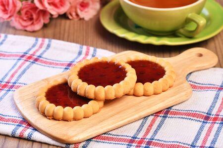 Raspberry jam tarts on wooden board