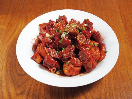 Braised pig knuckles with red yeast on white plate