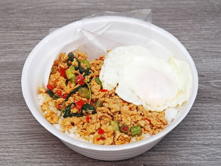 Stir fried minced pork with fried egg on rice in takeout food box for lunch. Reklamní fotografie