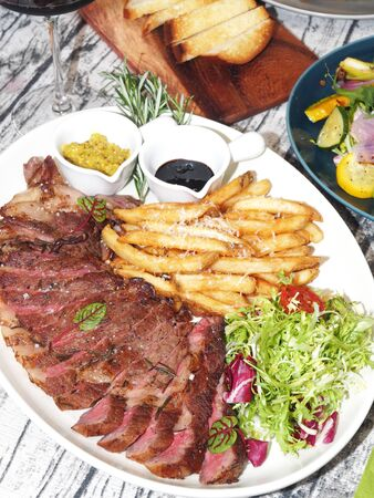 Rib eye steak with salad and french fries on a plate