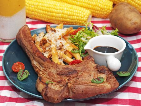 Barbecue tomahawk pork steak with salad and french fries on a plate