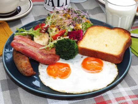 English breakfast with fried eggs, bacon, sausages, toasts and salad on the plate