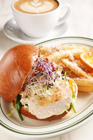 Grilled chicken breast burger with french fries on white plate