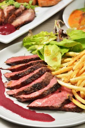 Roasted beef with french fries and salad on white plate