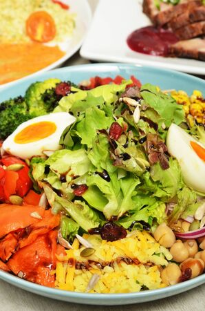 Healthy vegetable salad of fresh tomato, garbanzo beans, onion, broccoli, lettuce and boiled egg on plate