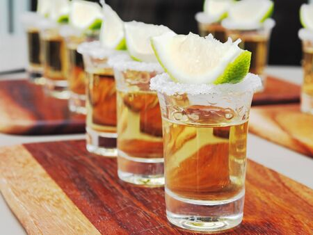 Tequila shots with lime and salt on the wooden tray. Reklamní fotografie