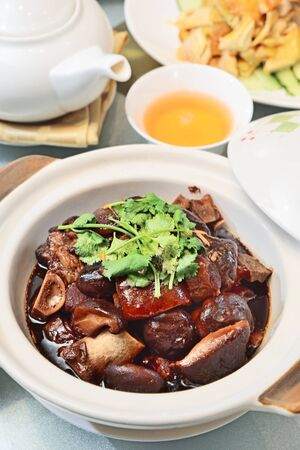 Delicious braised pork leg with brown sauce in ceramic pot