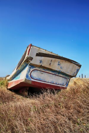 An abandoned fishing boat on dry brown grasses. Stock Photo