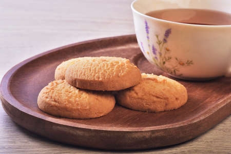 Close up of coconut cookies with tea on the wooden tray
