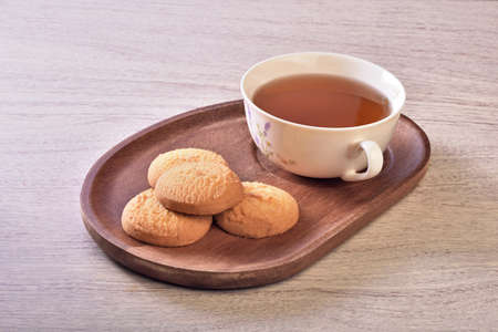 Coconut cookies with tea on the wooden tray