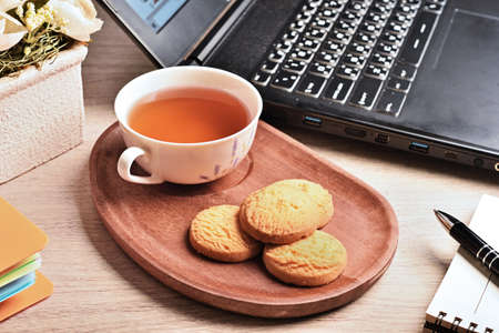 Coconut cookies with tea on the wooden tray in office