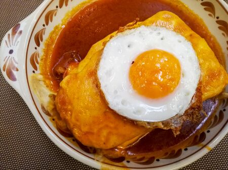 Francesinha with egg on top - portuguese traditional sandwich with the most delicious sauce and well cooked meat