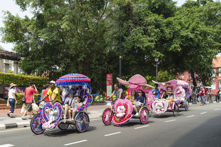 trishaw: Decorated trishaw with colorful flowers and doll for hire at Malacca city, Malaysia. - A popular historic tourist attraction and trishaw riding in Melaka, Malaysia. Editorial