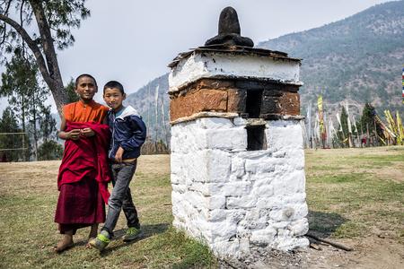 Neidentifikovaní mladí studenti se štěstím, kteří studují buddhismus u kláštera Chimi Lhakang, Punakha, Bhútán. - Chimi Lhakang je buddhistický klášter v okrese Punakha. Bhútán.