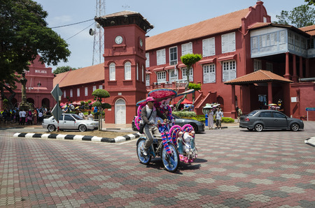 malaysia culture: Decorated trishaw with colorful flowers and doll for hire at Malacca city, Malaysia. - A popular historic tourist attraction and trishaw riding in Melaka, Malaysia. Editorial