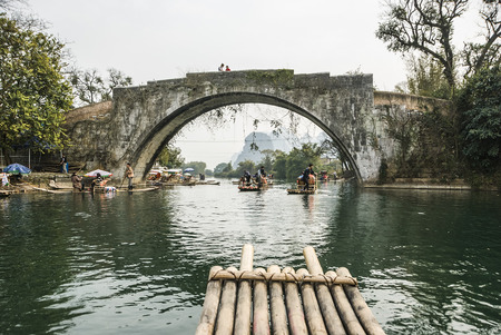 Guilin, China - Tourists taking bamboo raft rides during winter season in the Yulong River or Dragon River in Yangshuo near Guilin in southern China. - Bamboo rafting along Yulong River during the winter season with beauty of the landscape is a popular ac Editorial