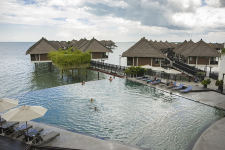 People cooling off and relaxing at swimming pool during seasonal summer holiday, Sepang, Malaysia