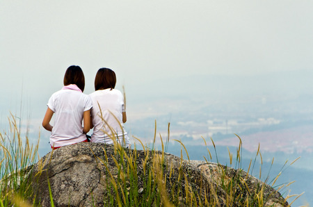 two young girls sit relax at mountain top