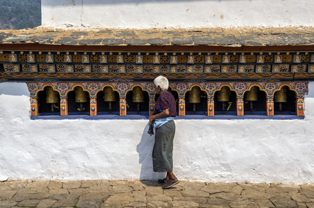 Unidentified women go around spinining the bhutanese praying wheel at Chimi Lhakang Monastery, Punakha, Bhutan.