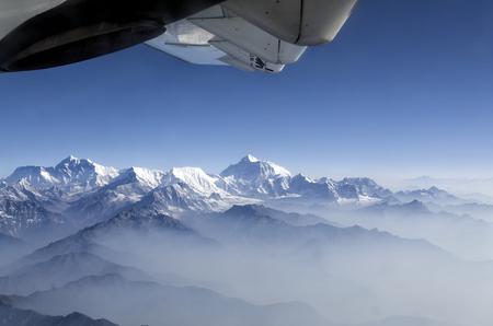 window view: Everest Peak and Himalaya Everest mountain range panorama view through plane window - Himalayas mountains Everest range panorama aerial view