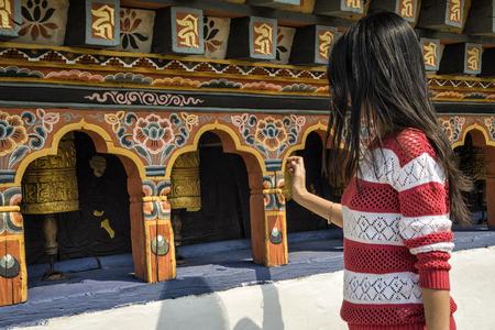 Neidentifikovaná dívka chodí kolem spinning bhutánského modlícího kolečka u kláštera Chimi Lhakang, Punakha, Bhútán.