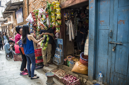 Visitors selecting and negotiating for goods along historic busy narrow street around Bhaktapur, Nepal.