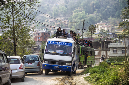 Road and transportation in Kathmandu, Nepal. Over crowded bus with passengers riding on roof in Kathmandu, Nepal Editorial