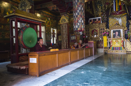 Unidentified tibetan monks praying and chanting inside buddhist temple near Boudhanath Stupa, Kathmandu, Nepal. Редакционное