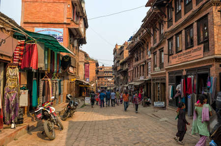 People walking on busy historical street around Bhaktapur that was partially destroyed at major earthquake in 2015, Kathmandu, Nepal
