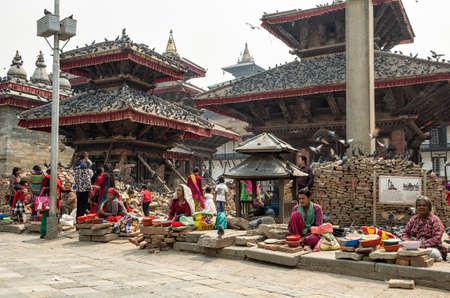 Unitendified women selling dry corn as bird feed at damaged Kathmandu Durbar Square after major earthquake in 2015. Kathmandu, Nepal.
