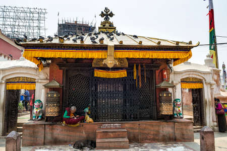 Unidentified buddhist pilgrim prayers and tourists at Boudhanath stupa, Kathmandu, Nepal. Boudhanath is a UNESCO world heritage site and is one of the largest ancient stupa in the world.