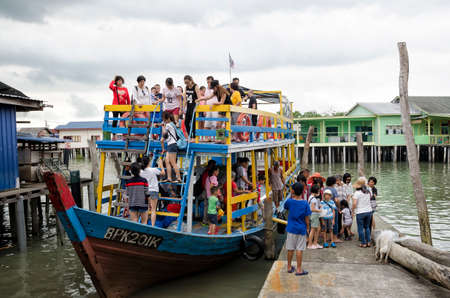 Unidentified tourists alighting from touring wooden boat at jetty in Pulau Ketam, Malaysia