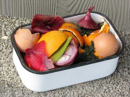 composting: Colorful kitchen compost in a vintage white enamel container. Natural light.  Stock Photo