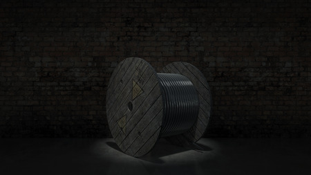 coax: Roll of black industrial underground cable on large wooden reel at construction site