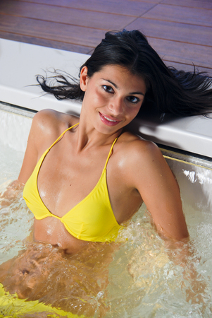 Young sexy brunette taking a hot tube hydromassage bath on a spa