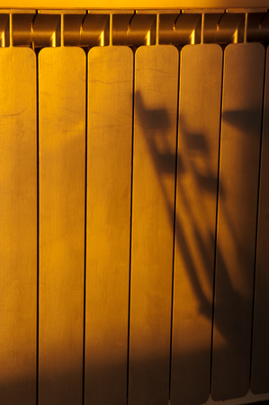 Silhouette chairs shadow reflected in an apartment radiator at sunset. Late spring season. Stock Photo