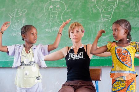 Malí, África - Circa agosto de 2009 - Mujer blanca enseñando a niños negros en un aula típica cerca de Bamako