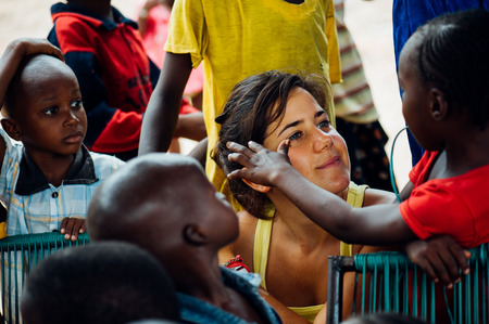 Mali, Africa - circa August 2009 - White caucasian young woman plays with black african people in a rural village near Bamako