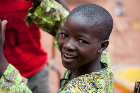 Mali, Africa - circa August 2009 - Black african boy looking happy at camera while  living in a rural area near Bamako
