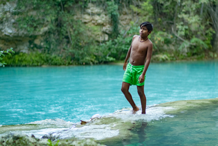 Latin boy having fun getting a bath in the middle of October on a turquoise water river. Global warming affects water temperature. SentierElsa, Colle Val dElsa. Tuscany Italy Europe