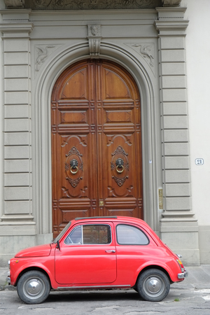 Red outdoor model parked in the city. Fiat 500 last century vintage car. 1950 1960 1970 1980 1990 Tuscany  Italy Europe