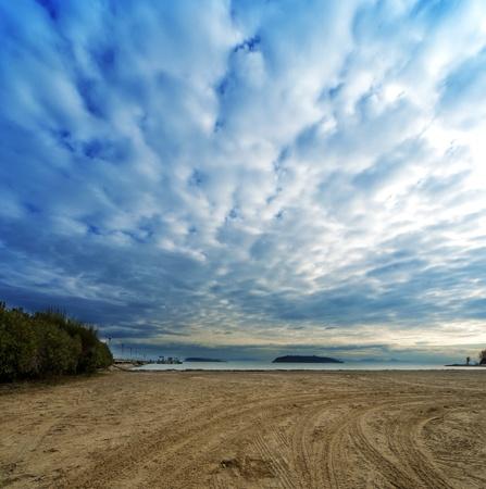 beach on trasimeno lake river with islets far away