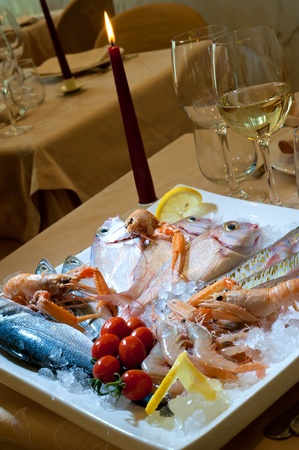 raw fishes and crafwfishes with freh tomato on a restaurant table