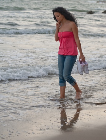 a young brunette european girl walking in the water