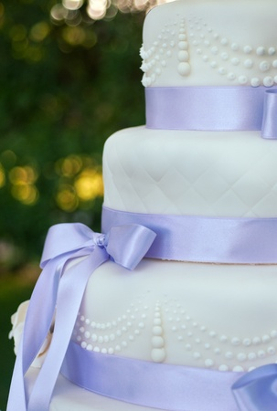 wedding cake: details on a wedding cake with violet ribbons and decorations Stock Photo